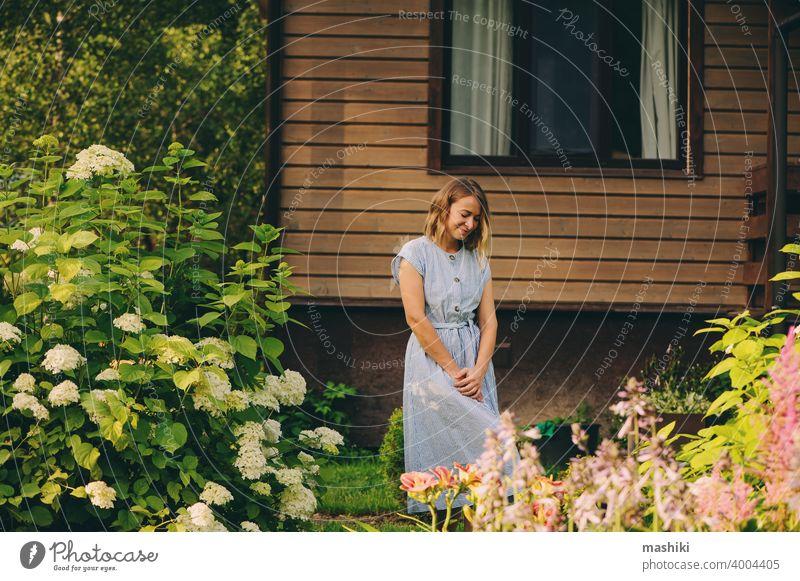 Junge glückliche Frau, die in einem privaten Garten spazieren geht, posiert an einem hölzernen Landhaus. Gartenarbeit Pflanze Glück Kaukasier Lifestyle Gärtner