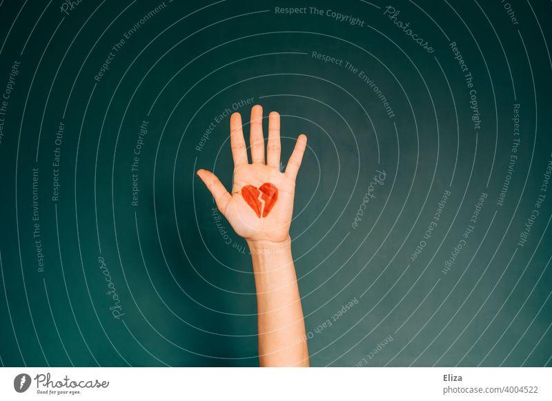 Hand mit einem gemalten zerbrochenen Herzen. Konzept Liebeskummer und Trennung. Beziehungsende Gefühle rot Partnerschaft Probleme Liebesaus Schluss machen Ende