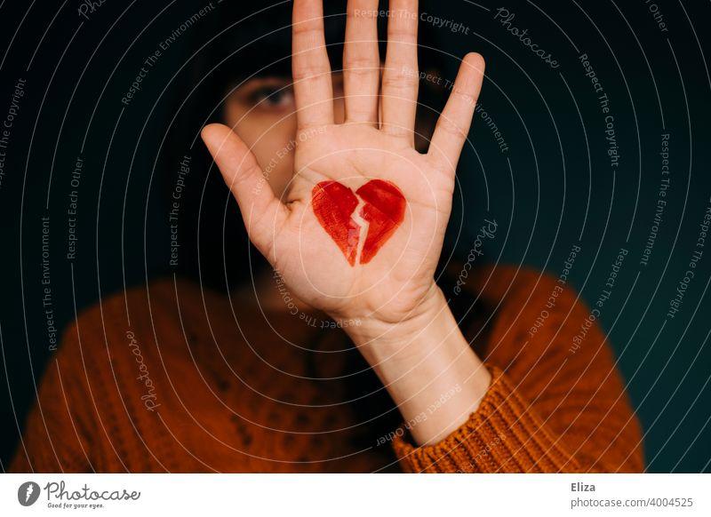 Eine Frau hält die Hand, auf der ein zerbrochenes rotes Herz gemalt ist, vors Gesicht. Konzept Liebeskummer. Beziehungsende Gefühle Partnerschaft Probleme