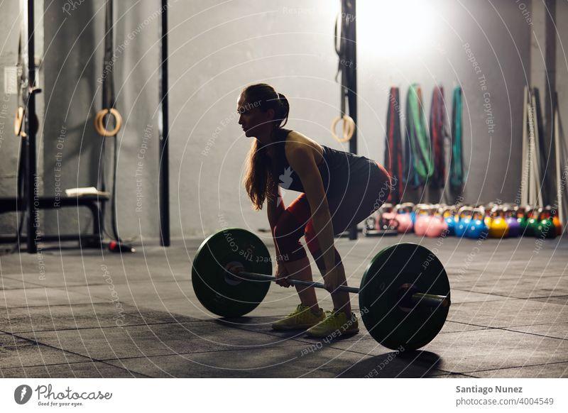 Kaukasische Frau hebt eine Langhantel. Crossfit Funktionstraining Fitnessstudio Gesundheit Sport Training Übung Lifestyle passen Erwachsener Vitalität