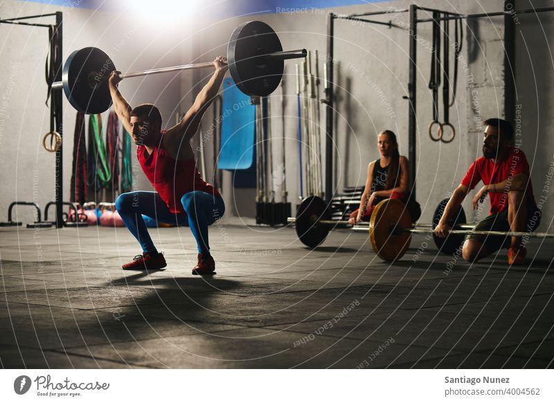 Mann hockt und hebt eine Langhantel. Crossfit Funktionstraining Fitnessstudio Gesundheit Sport Training Übung Lifestyle passen Erwachsener Sportbekleidung