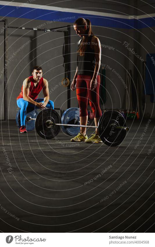 Frau hockt und hebt eine Langhantel. Crossfit Funktionstraining Fitnessstudio Gesundheit Sport Training Übung Lifestyle passen Erwachsener Sportbekleidung