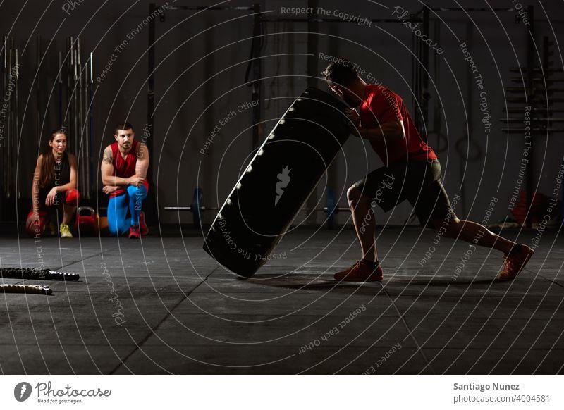 Frau kippt über einen Traktorreifen. Crossfit Funktionstraining Fitnessstudio Gesundheit Sport Training Übung Lifestyle Erwachsener Sportbekleidung Gerät Raum