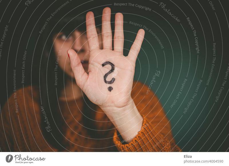 Eine Frau hält ihre Hand, auf die ein Fragezeichen gemalt ist, hoch. ratlos Verwirrung Identität Unsicherheit Irritation Fragen unsicher Unentschlossenheit