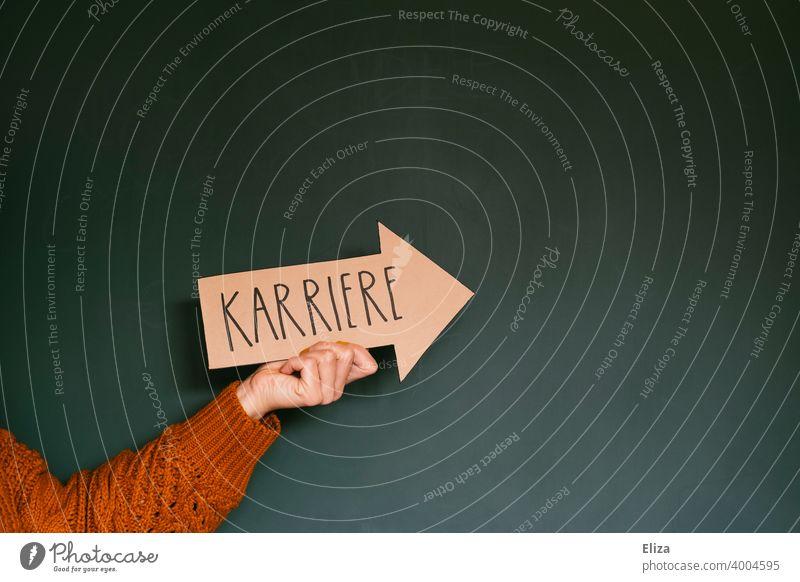 Hand hält einen Pfeil auf dem das Wort Karriere steht Erfolg Richtung Orientierung Business Zukunft richtungweisend erfolgreich Karriere machen