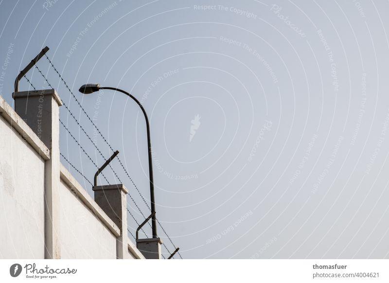 Mauer mit Stacheldraht und Flutlicht Gefängnismauer Stacheldrahtzaun Wand Himmel eingesperrt Überwachung Bewachung gefangen Schutz Grenze Sicherheit Freiheit