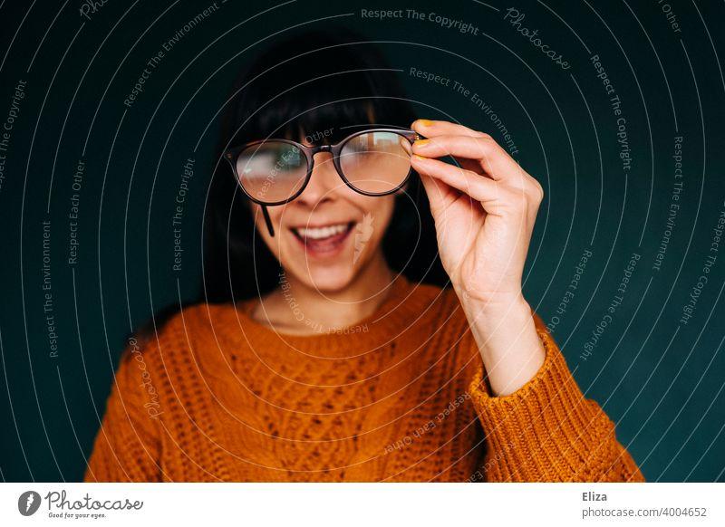 Frau guckt durch eine Brille und lacht dabei lachen lustig albern sehen verschwommen vergrößert Qautsch Grimasse Gesicht Auge Freude