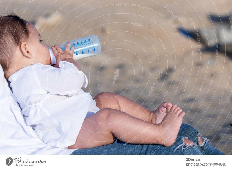 Neugeborenes trinkt Milch aus einer Babyflasche, sitzt auf Mama Beine im Freien neugeboren Flasche melken Kind Säugling Mutter Gesundheit Pflege niedlich Person