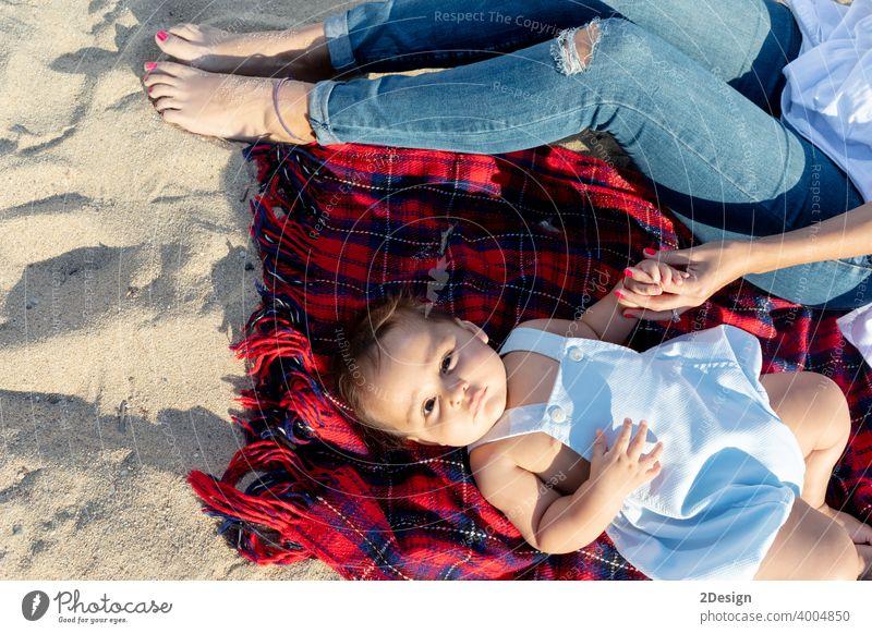 Lächelnde Mutter spielt mit Neugeborenen auf Strandtuch liegend Baby neugeboren Liebe Lügen Familie Fröhlichkeit Frau Person Handtuch Lachen Sand Sonnenlicht