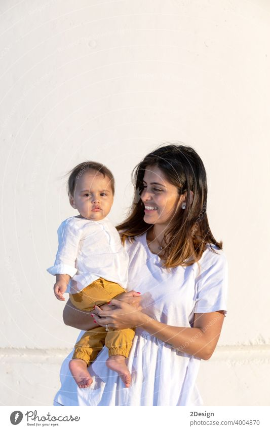 Junge Mutter hält ihr kleines Baby gegen weiße Wand in sonnigen Tag Kind neugeboren Liebe Familie Frau Pflege Beteiligung wenig Mutterschaft jung Kindheit