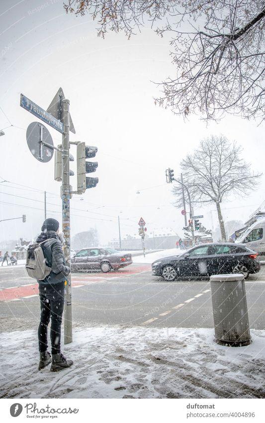 Mann wartet bei Schneegestöber an befahrener Kreuzung Winter weiß urban Stadt schneien frieren Eis kalt Schneefall Schneeflocke Ampel Verkehr Außenaufnahme