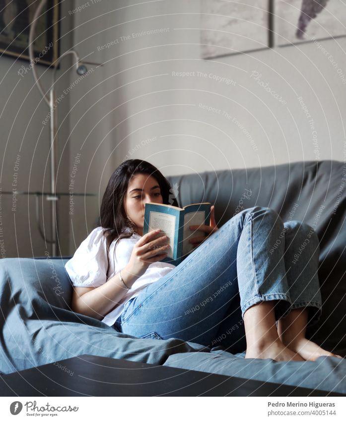 Frau lesend auf einem Sofa in einem Haus heimwärts Freizeit Sitzen bequem Wohnzimmer Kaukasier Lifestyle brünett im Innenbereich häusliches Leben
