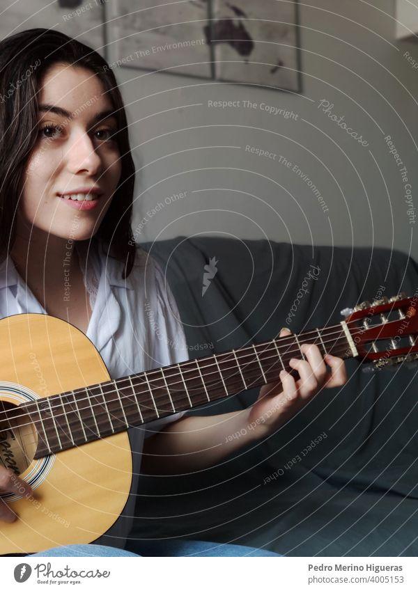 Frau spielt die Gitarre auf einem grauen Sofa Kaukasier Musical Musiker Mädchen Instrument Hintergrund Freizeitkleidung Schnur Atelier jung Lernen akustisch