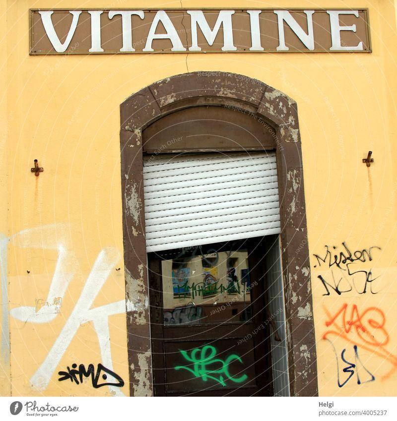 krumm und schief - marode Eingangstür mit schiefer Jalousie in gelber Wand mit Schmierereien und dem Schriftzug VITAMINE über der Tür Fassade alt kaputt