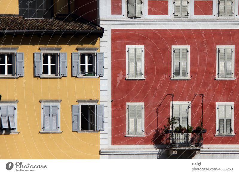 Fassaden,rot und gelb gestrichen mit weißen und grauen Fenstern und Fensterläden, ein Balkon Haus Gebäude farbig Fensterladen Architektur Außenaufnahme alt