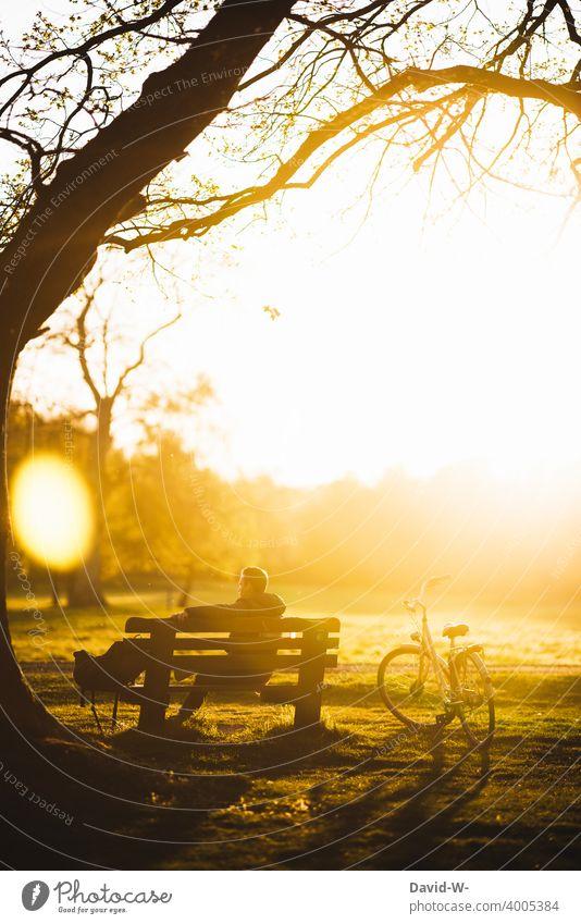 Radtour - Mann ruht sich im Sonnenlicht etwas aus und macht eine Pause Auszeit Sonnenuntergang Fahrrad Bank sitzen Natur draußen abschalten Schönes Wetter