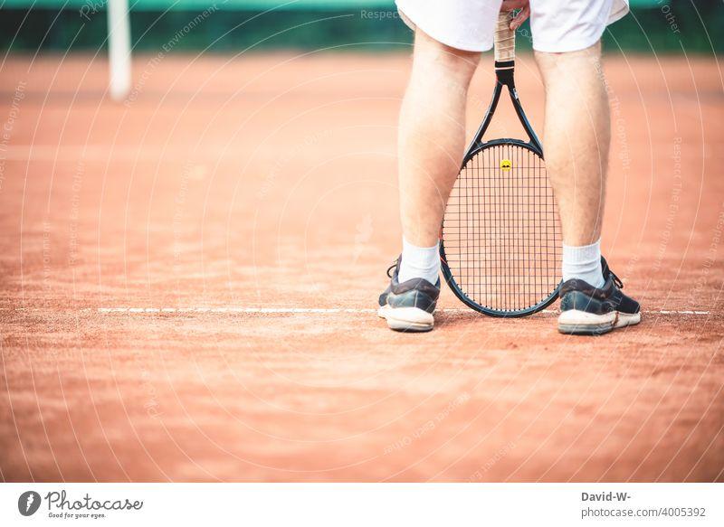 Mann steht lässig mit einem Tennisschläger auf dem Tennisplatz Sport Sportler cool sportlich Freizeit & Hobby