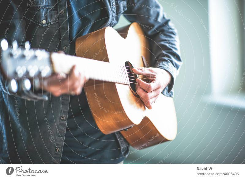 Mann spielt eine Gitarre Musik Musiker Musikinstrument Kultur lernen üben Spaß hobby Hobbys Hand Finger musizieren