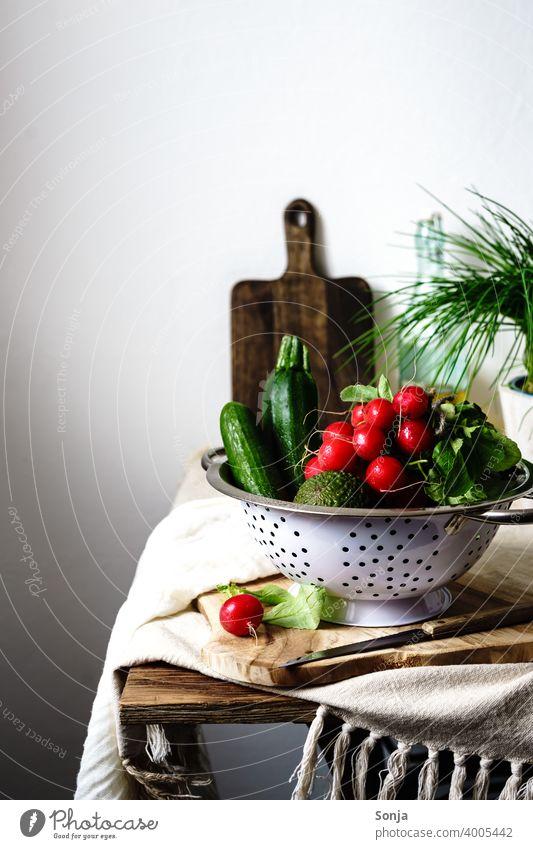 Stillleben von Gemüse in einem Sieb auf einem Küchentisch Radieschen grün Vegetarische Ernährung ländlich Bioprodukte frisch Gesunde Ernährung Diät natürlich