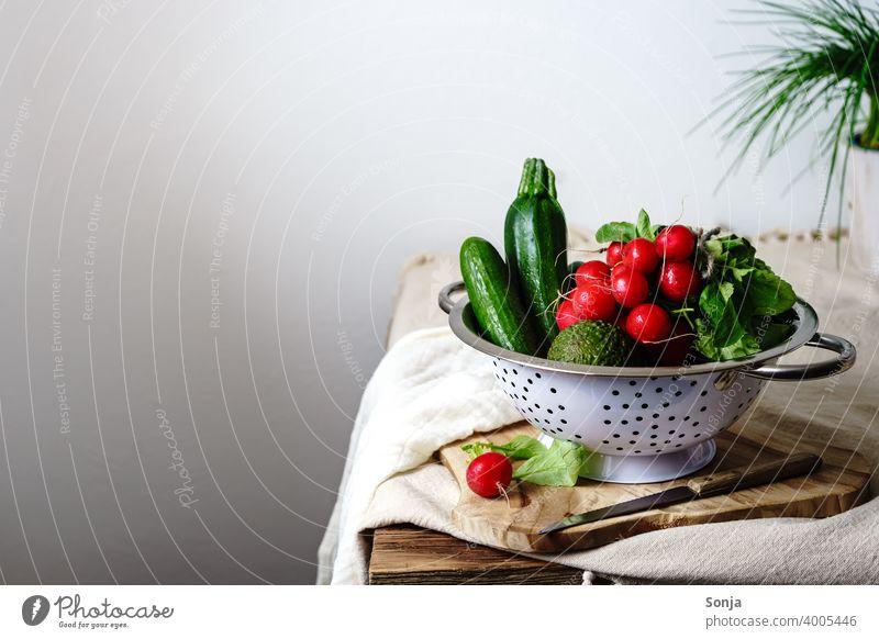 Rohe Radieschen und grünes Gemüse in einem Sieb auf einem Küchentisch roh Stillleben ländlich Vegetarische Ernährung Gesunde Ernährung Bioprodukte Diät