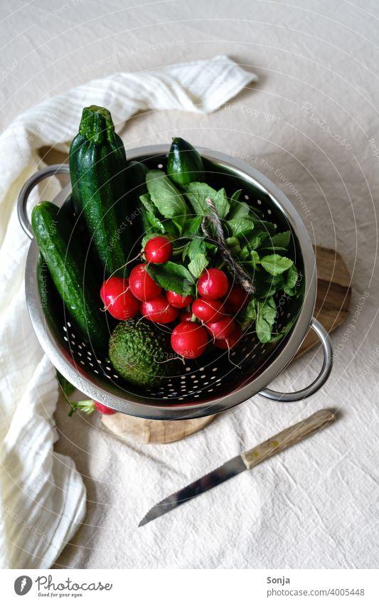 Radieschen und grünes Gemüse in einem Sieb auf einem beigen Leinen Tischtuch roh tischtuch Gesundheit Lebensmittel Vegetarische Ernährung organisch frisch Diät