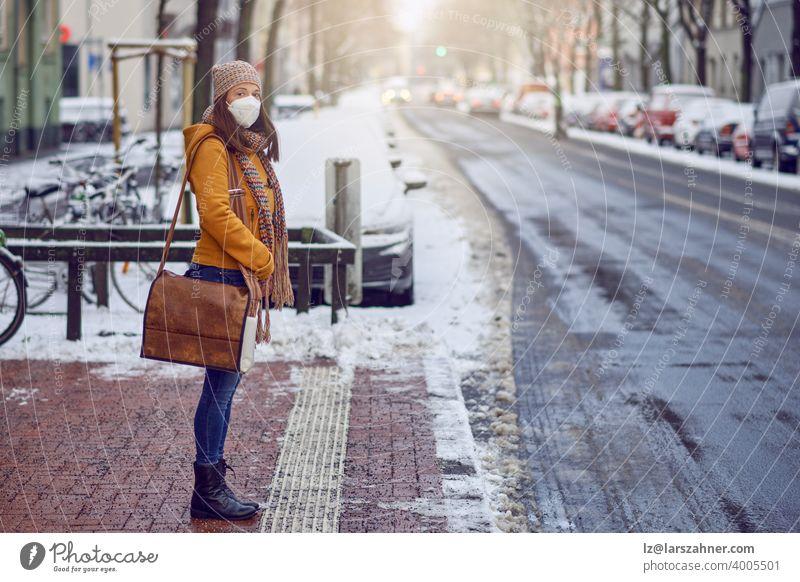 Brünette Frau mittleren Alters, die an einer Bushaltestelle steht, eine schützende Gesichtsmaske aufgrund des Coronavirus trägt und auf ihren Bus wartet, der sie zur Arbeit bringt