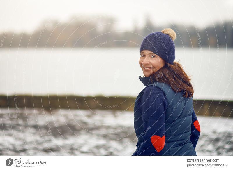 Glückliche brünette Frau mittleren Alters im Pullover mit Strickmütze dreht sich um und schaut in die Kamera sich[Akk] wandelnd Gesicht Porträt Winter Lächeln