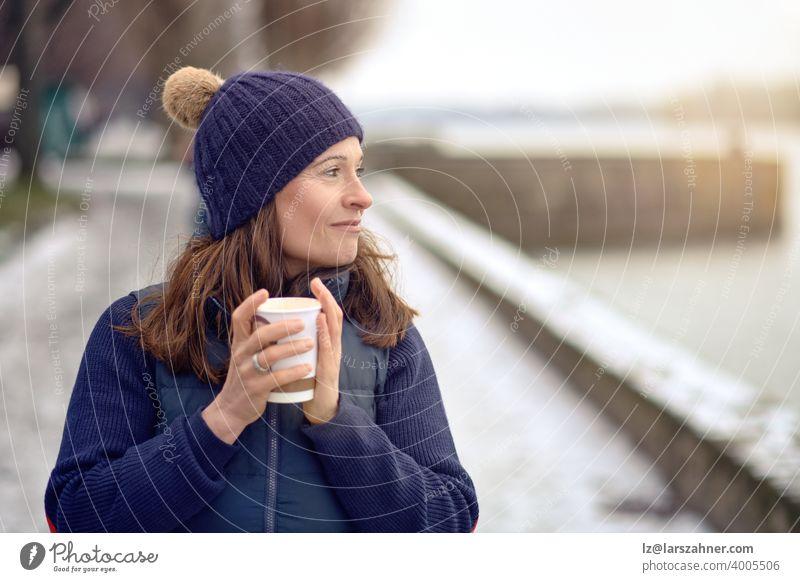 Glückliche brünette Frau mittleren Alters geht spazieren und trinkt einen Kaffee zum Mitnehmen trinken Getränk im Freien gehen Tee reif Lifestyle Generation