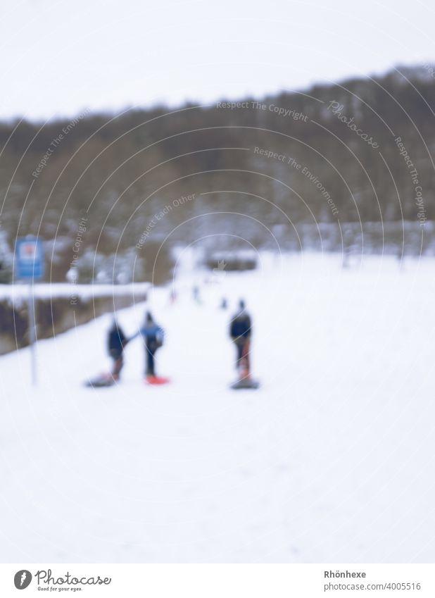 Kinder im Dorf beim Schlittenfahren unscharf fotografiert schlittenfahren Winter Schnee kalt Natur weiß Rodeln Freude Farbfoto Außenaufnahme Freizeit & Hobby