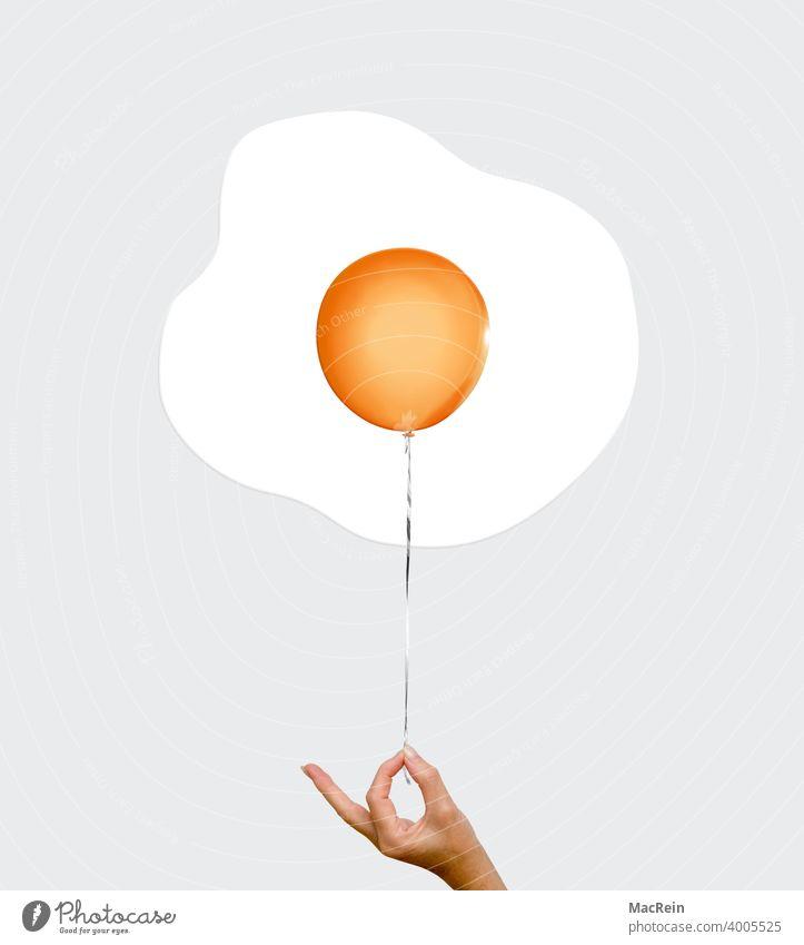 Spiegelei ballon eigelb eidotter faden farbaufnahme festhalten finger hand orange spiegelei niemand textfreiraum symbolbild