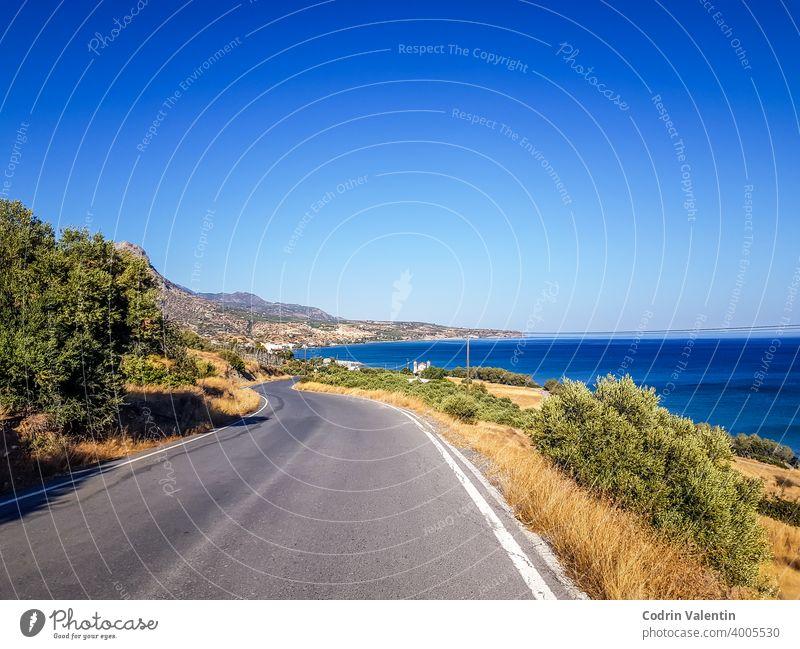 Küstenlinie und eine kurvenreiche Straße in Keratokampos, Kreta Asphalt Bucht Strand Cloud Ökoregion Fernstraße Gras grün Autobahn Horizont Insel See Landschaft