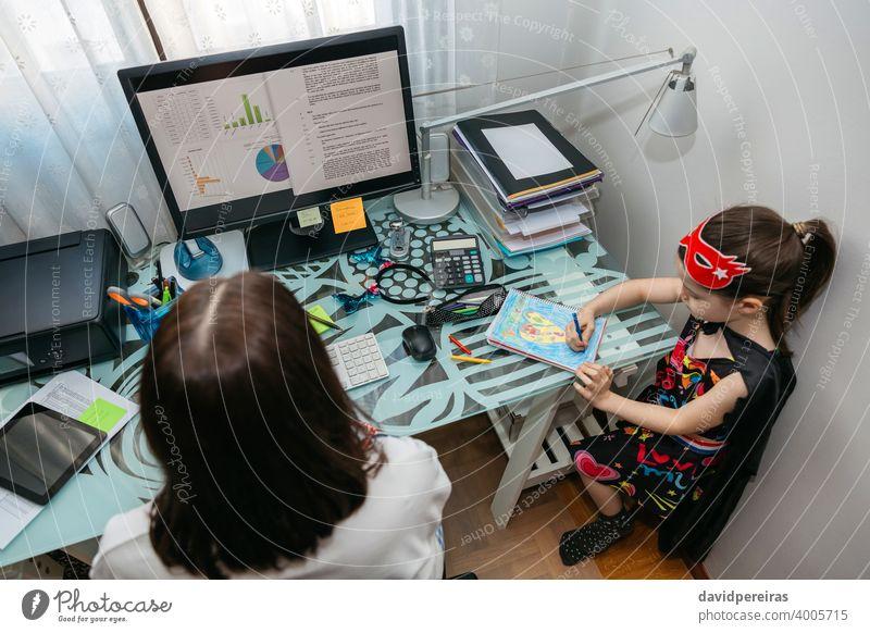 Frau bei Telearbeit mit ihrer Tochter beim Zeichnen Overhead Coronavirus covid-19 Quarantäne Einsperrung Computer Draufsicht Vereinbarkeit von Familienarbeit