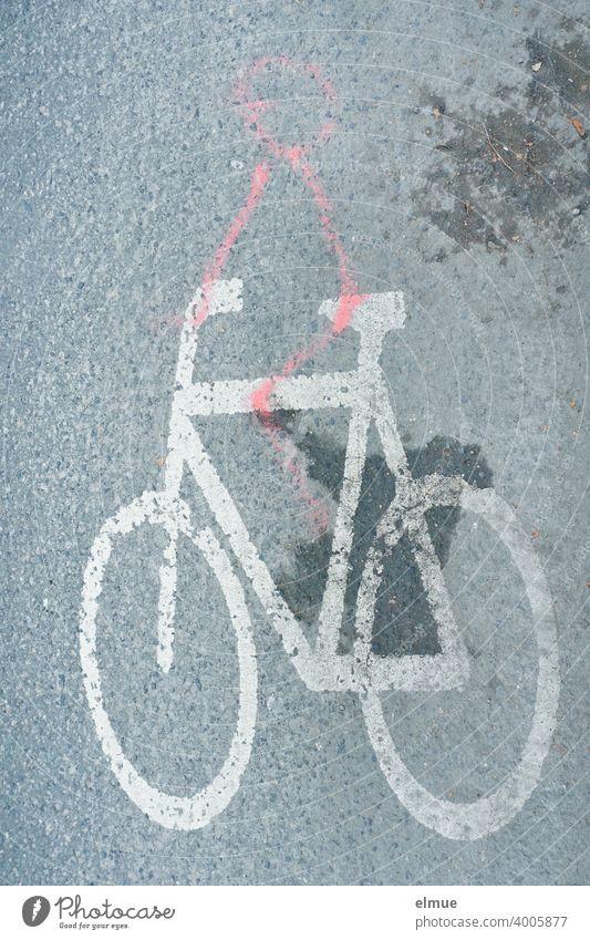 Ein Spaßvogel hat mit roter Farbe ein Strichmännchen auf ein weißes Fahrrad - Piktogramm auf der grauen, asphaltierten Straße gemalt / Straßenmarkierung Humor