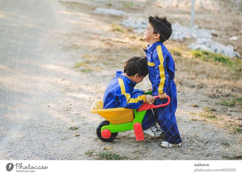 Fröhliche und lächelnde Kinder haben Spaß auf dem Feld mit einer Schubkarre Brüder Geschwister Zwillinge Glück Lächeln Freundschaft elementar primär Babys