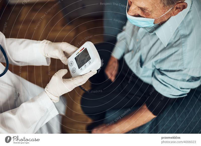 Der Arzt prüft den Blutdruck und die Herzfrequenz eines älteren Mannes. Überprüfung des Gesundheitszustands älterer Patienten, die an arterieller Hypertonie leiden