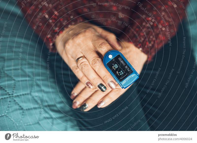 Frau misst den Grad der Sauerstoffsättigung des Blutes und der Herzfrequenz zu Hause mit Pulsoximeter. Behandlung von Viren zu Hause. Überprüfung des Gesundheitszustandes
