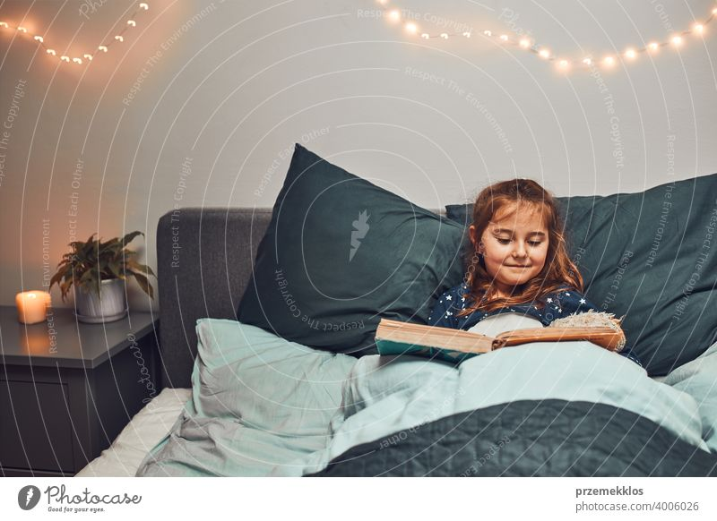 Kleines Mädchen lesen Buch und beobachten Bilder im Bett vor dem Schlafengehen. Gutenachtgeschichten für Kind Nacht Schlafenszeit Familie heimwärts Literatur