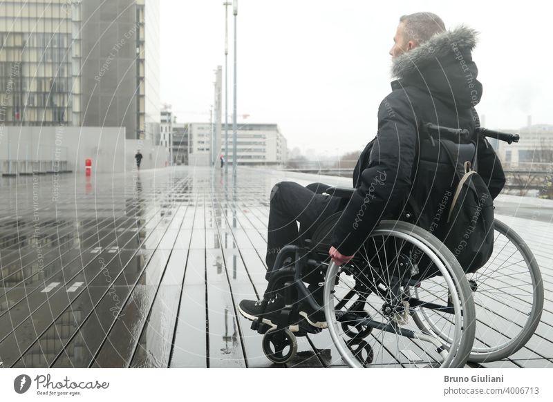 Konzept einer behinderten Person. Ein Mann in einem Rollstuhl draußen auf der Straße. medizinisch deaktiviert querschnittsgelähmt Behinderung Gerät Behinderte