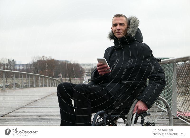 Konzept der behinderten Person. Mann in einem Rollstuhl draußen auf der Straße. Menschen mit Technologie mit Smartphone. Gerät querschnittsgelähmt verbunden