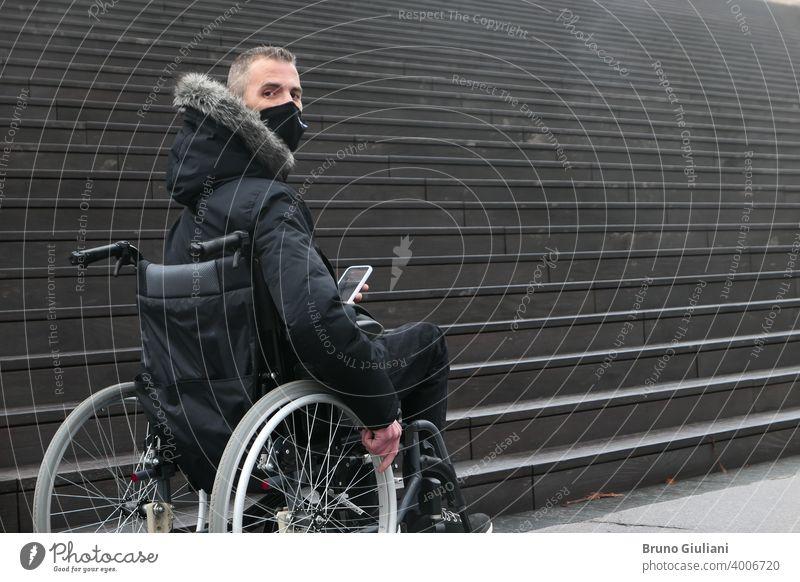 Konzept der behinderten Person. Mann in einem Rollstuhl draußen auf der Straße vor der Treppe. Menschen mit Smartphone. Operationsmaske deaktiviert