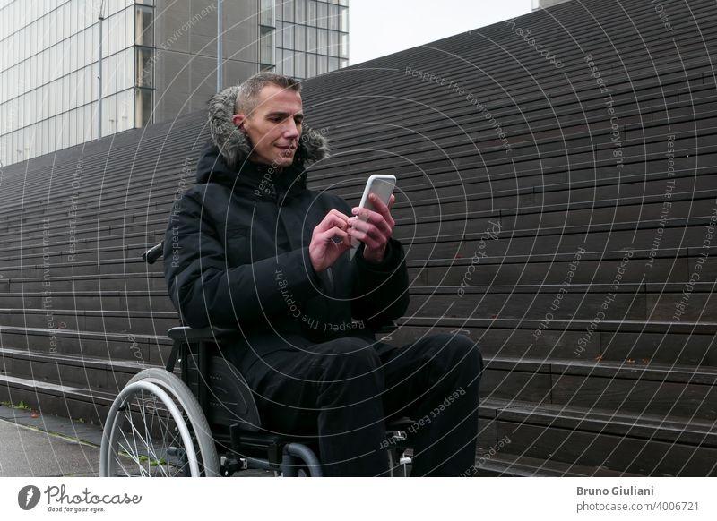 Konzept der behinderten Person. Mann in einem Rollstuhl draußen auf der Straße vor der Treppe. Menschen mit Technologie mit Smartphone. deaktiviert Behinderung