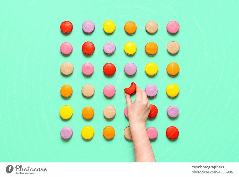 Macarons symmetrisch auf einem farbigen Hintergrund ausgerichtet. Frau Hand nimmt eine Makrone, Ansicht von oben obere Ansicht Mandelplätzchen Handwerklich