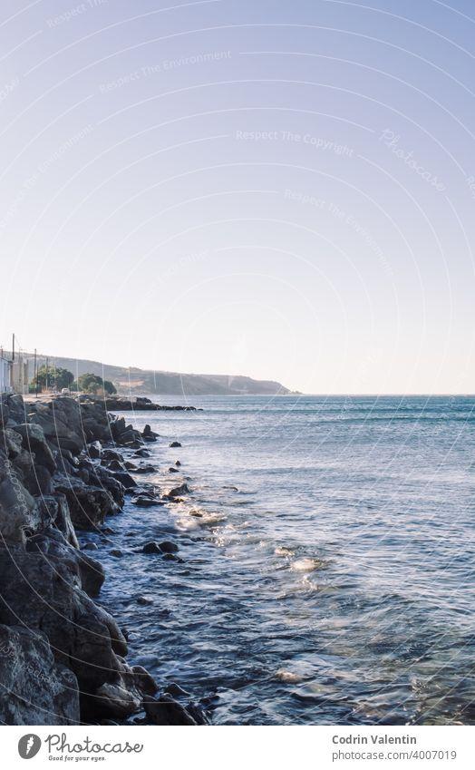 Küstenlinie mit kleinen Wellen und Felsen Architektur Bucht Strand Boot Körper Klippe Cloud Küsten- und ozeanische Landformen Abenddämmerung Vorgewende Horizont