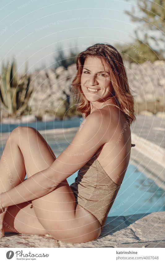 Junge Frau im einteiligen Badeanzug entspannt neben dem Schwimmbad rot tropisch Pool Wasser Sommer jung Kaukasier Mode allein Glück Lächeln Garten Emotion