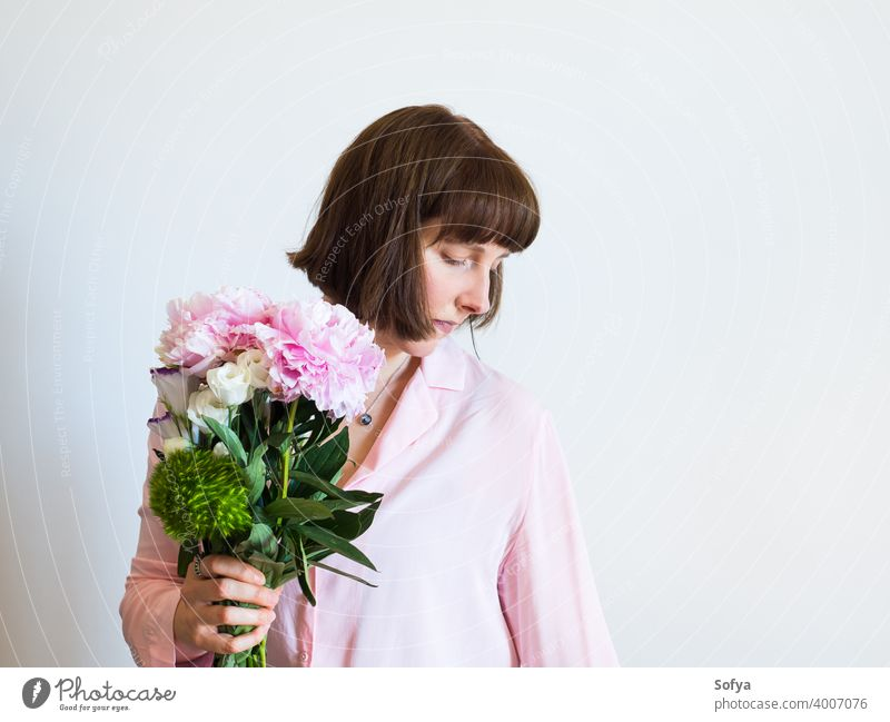 Junge Frau hält schöne Pastell Pfingstrose Bouquet Mutter Tag Blumenhändler Muttertag Frühling Gesicht rosa Lifestyle Frauentag Blumenstrauß Lächeln Ausdruck