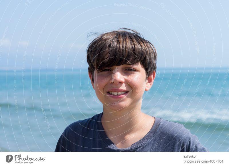 Porträt eines lächelnden männlichen Teenagers gegen blaues Meer Kaukasier Jugendzeit Lifestyle Strand jung 1 Person niedlich Behaarung Sommer Junge heiter