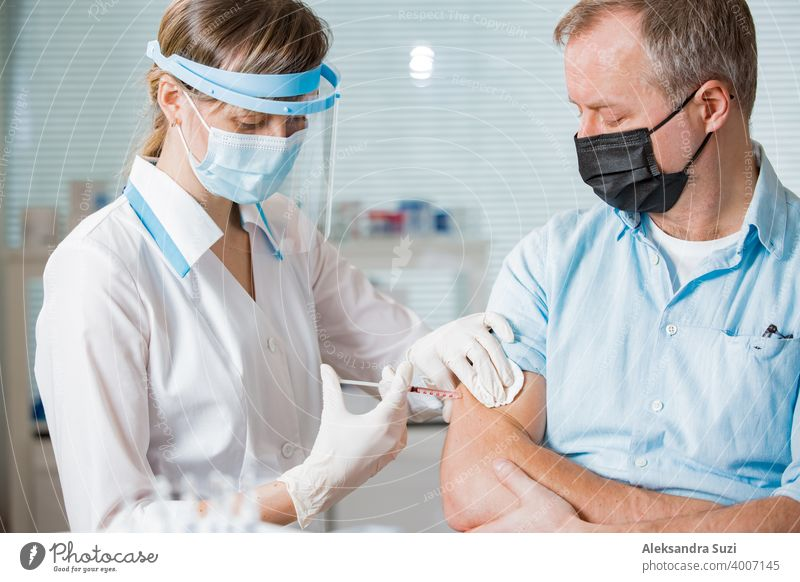 Eine Ärztin mit chirurgischer Maske und in Handschuhen gibt einem Mann im Krankenhaus eine Impfstoffinjektion. Impfung während der COVID-19-Pandemie Arme Pflege