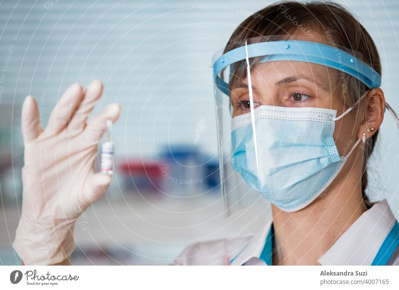 Ärztin mit OP-Maske und in Handschuhen hält Impfstoffampulle und Spritze. Impfung während der COVID-19-Pandemie Arme Pflege Klinik Coronavirus covid-19 Kur