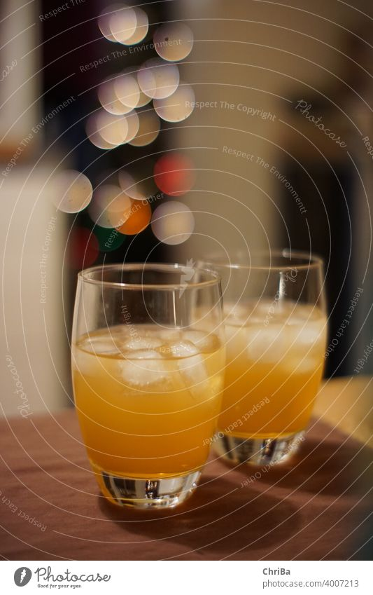 Drinks mit Eis und Lichter Bokeh eiswürfel getränk getränke alkohol gläser anstoßen orange bitter kräuter weihnachten festlich glamour bokeh glitzer