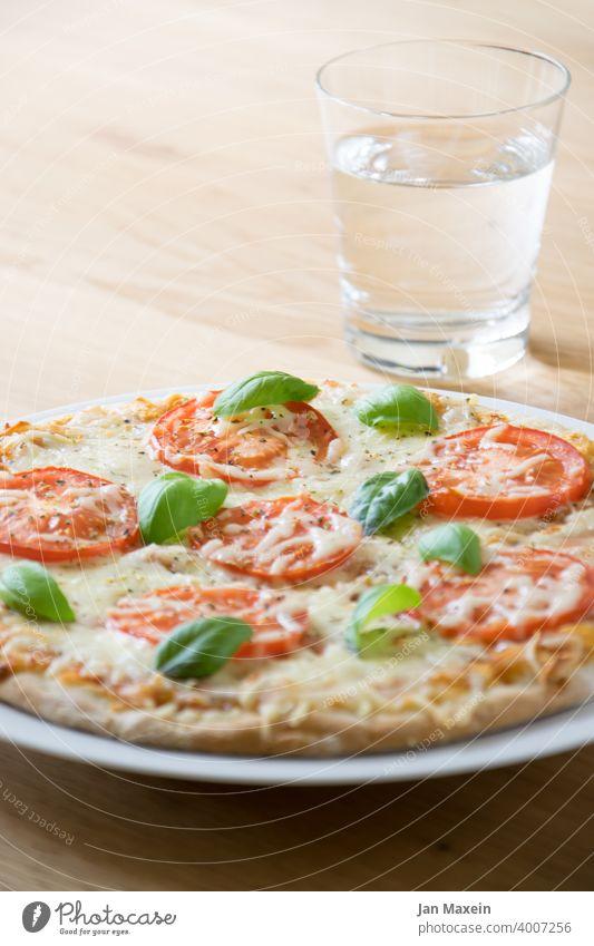 Pizza mit Tomate und Basilikum, dazu ein Glas Wasser Pizzateig hefeteig Käse Mozzarella Italien Holz Holzti Lebensmittel Gemüse Ernährung Italienisch Mahlzeit